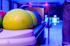 Le palle da bowling gialle ha pronto per il giocatore alla palla di lancio sopra Fotografia Stock