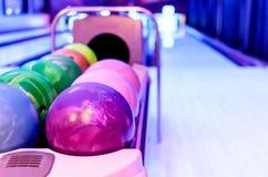 Le palle da bowling porpora ha pronto per il giocatore alla palla di lancio sopra Immagini Stock