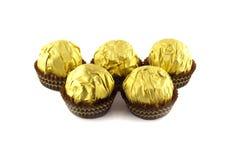Le palle del cioccolato wraped nel pacchetto dorato isolato su bianco Fotografia Stock Libera da Diritti