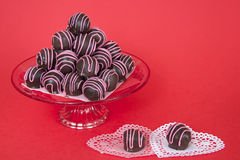 Le palle del dolce di cioccolato hanno spogliato le colate rosa della caramella impilate sul piatto Fotografie Stock Libere da Diritti