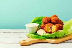 Le palle del Falafel sono servito con la salsa di tahini e della pita su un bordo di legno Immagine Stock Libera da Diritti