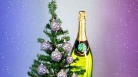Le palle del nuovo anno su un albero del nuovo anno e su una bottiglia enorme di vino spumante stock footage