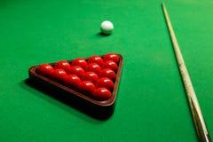 Le palle dello snooker su una tavola di biliardo inseriscono la palla bianca Immagine Stock