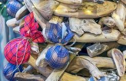 Le palle di Natale hanno annodato in un tessuto del plaid su un albero di Natale di legno fotografia stock