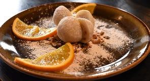 Le palle di riso del dessert, la palla del gelato ed i pezzi di frutti sono servito su un piatto scuro Immagine Stock