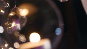 Le palle di vetro con le candele appendono prima della finestra stock footage