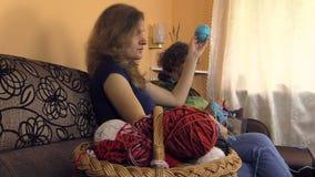 Le palle e la donna della lana del canestro rotolano la palla blu la nonna tricotta i calzini stock footage