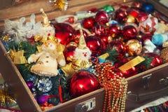 Le palle ed il pupazzo di neve di Natale giocano in vecchia valigia Immagine Stock
