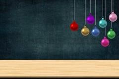 Le palle variopinte di natale orna l'attaccatura nella classe di scuola con lo scrittorio sul fondo della lavagna Spazio della co Fotografia Stock