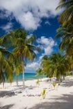 Le palme ed i loungers su una sabbia bianca tirano Fotografia Stock Libera da Diritti
