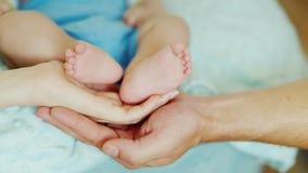 Le palme mamma e papà tengono i piccoli piedi del bambino dei piedi stock footage