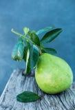 Le pamplemousse avec le vert part sur un conseil en bois Photographie stock libre de droits