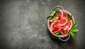 Le pamplemousse de coupe avec des feuilles dans une casserole Photographie stock libre de droits