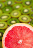 Le pamplemousse mûr frais avec le vert a découpé le kiwi en tranches sur le fond Photos libres de droits