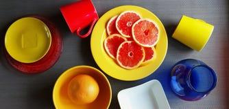 Le pamplemousse rouge découpe l'assiette creuse en tranches rose jaune rouge vert-bleu de plats de pulpe juteuse de pomme d'agrum image stock