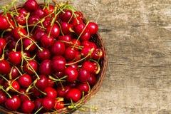 Le panier avec la merise rouge porte des fruits sur la table en bois de vintage Images stock