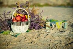 Le panier avec les pommes et les bananes rouges sur la plage Image stock
