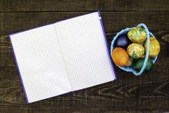 Le panier bleu avec des oeufs de pâques sur un fond en bois brun foncé, a dévoilé le carnet pour l'espace de copie images libres de droits