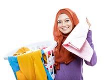 Le panier de blanchisserie de transport de port de hijab de femme au foyer et prennent un photographie stock libre de droits