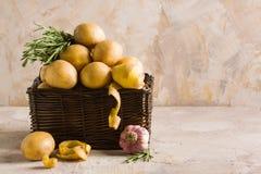 Le panier en bois avec les pommes de terre et le romarin de peaux poivrent Image libre de droits
