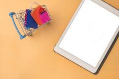 Le panier et le chariot de papier colorés vont vers le bas de flotter le fond rose pour l'espace de copie images stock