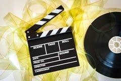 Le panneau de clapet avec des cadres de jaune de film de 35mm et le film tournoient Photo stock