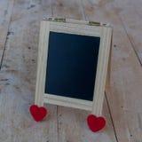 Le panneau de menu aux coeurs noirs et rouges a placé sur un plancher en bois Photos stock