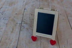 Le panneau de menu aux coeurs noirs et rouges a placé sur un plancher en bois Photo stock