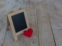 Le panneau de menu aux coeurs noirs et rouges a placé sur un plancher en bois Images stock