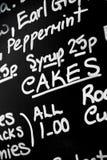 Le panneau de menu de craie écrit par main a comporté le prominentl de gâteaux de mot photos stock