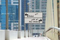Le panneau routier indiquant la direction de Dubaï et d'Abu Dhabi, le choix doit être fait à la prochaine intersection image stock