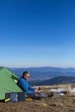Le panneau solaire fixé à la tente L'homme s'asseyant à côté du téléphone portable charge du soleil Photos stock