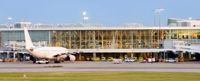 Le panorama d'un aéroport moderne et des avions blancs dans la lumière électrique s'allume Photographie stock