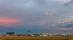 Le panorama d'un aéroport moderne et des avions blancs dans la lumière électrique s'allume dans la perspective d'un ciel de soiré Photos stock