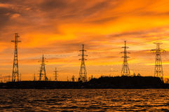 Le panorama des lignes électriques à haute tension s'approchent de l'eau au coucher du soleil Image stock