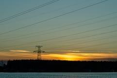 Le panorama des lignes électriques à haute tension s'approchent de l'eau au coucher du soleil Photographie stock libre de droits