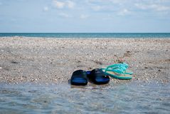 Le pantofole maschii e femminili delle scarpe da tennis sulla spiaggia innaffiano l'estate del cielo blu Fotografia Stock