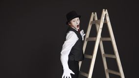 Le pantomime d'homme monte l'échelle, regarde autour, courant à partir d'une bête imaginaire clips vidéos
