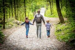 Le papa avec ses enfants marche par derrière dedans les bois images stock