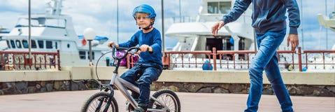 Le papa enseigne le fils à monter un vélo dans la BANNIÈRE de parc, long format photographie stock