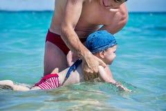 Le papa enseigne le jeune fils à nager en mer Photo stock