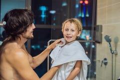 Le papa essuie son fils avec une serviette après une douche le soir avant d'aller dormir sur le fond d'une fenêtre avec a photographie stock