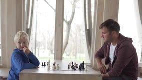 Le papa et le fils jouent aux échecs dans un club d'échecs clips vidéos