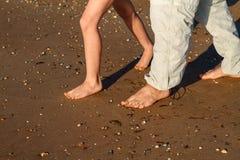 Le papa et le fils marchent sur la plage nu-pieds images libres de droits