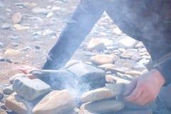 Le papa et le fils mettent à feu les charbons dans le feu sur le brasero de pierres avec les bâtons en bois photographie stock
