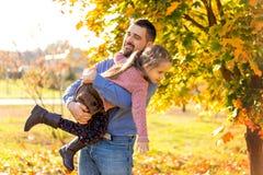 Le papa et la fille en parc d'automne jouent rire image stock