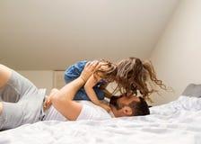 Le papa et la fille ont l'amusement à la maison sur le lit Jour du `s de père images libres de droits