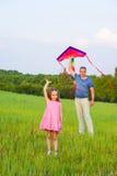 Le papa et la fille pilotent un cerf-volant Image stock