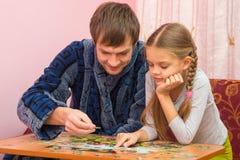 Le papa et la fille rassemblent avec enthousiasme la photo des puzzles photographie stock
