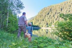 Le papa et la fille vont pêcher ensemble dans un lac de montagne photos libres de droits